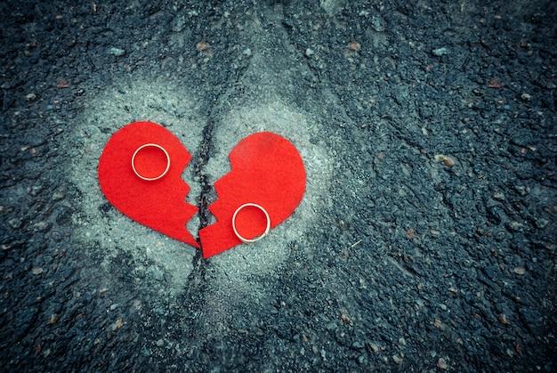 Scheidingsconcept - gebroken hart met trouwringen op gebarsten asfalt. afgezwakt