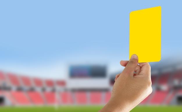 Scheidsrechter die gele kaart in het veld