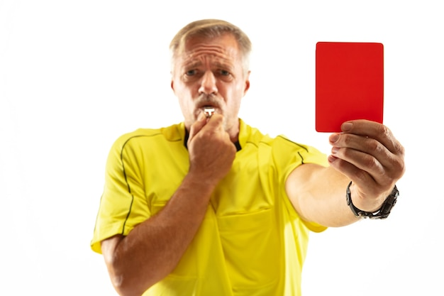 Scheidsrechter met een rode kaart en gebaren naar een voetbal of voetballer tijdens het gamen geïsoleerd op een witte muur. concept van sport, overtreding van regels, controversiële kwesties, obstakels overwinnen.