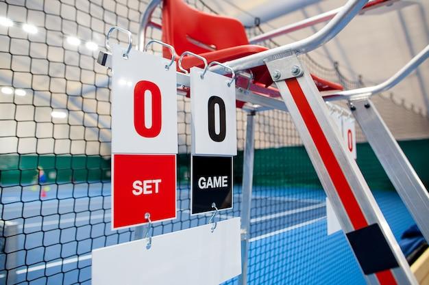 Scheidsrechterstoel met scorebord op een tennisbaan vóór de wedstrijd