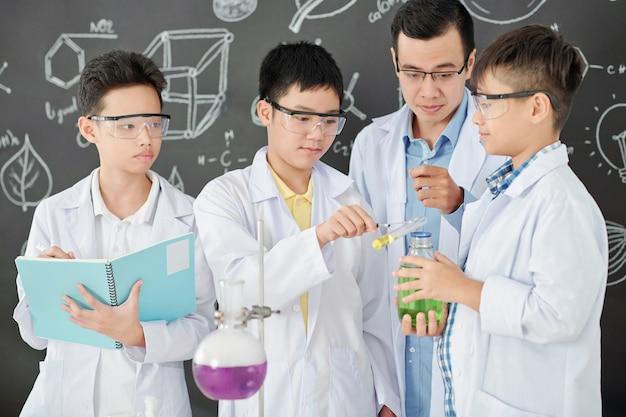 Scheikundeleraar die scholieren controleert die kleurrijke vloeistoffen mengen en aantekeningen maken in beurt