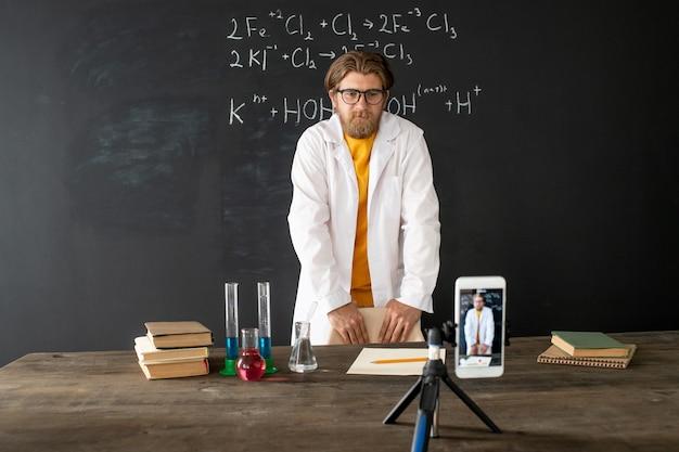 Scheikundeleraar in whitecoat permanent door bord voor smartphone tijdens het fotograferen zichzelf tijdens online les