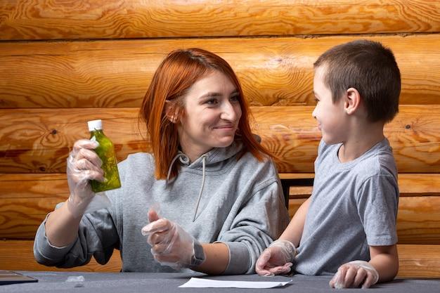 Scheikundeonderwijs en studieconcept. een kleine jongen en zijn moeder schudden een fles met een oplossing om de reactie thuis te versnellen.