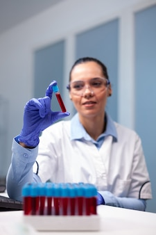 Scheikundige arts die dna-bloed analyseert met behulp van medische vacutainer die werkt bij microbiologisch experiment