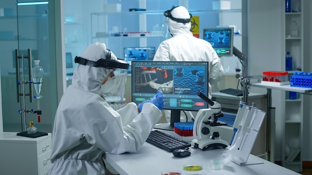 Scheikundige arts in pbm-pak aan het werk op pc terwijl laboratoriumtechnicus haar bloedmonsters brengt