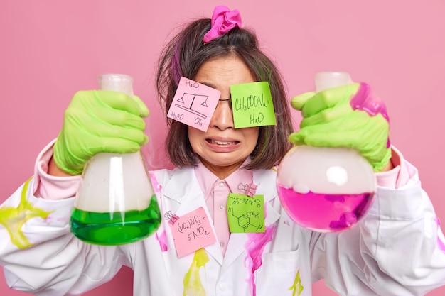 Scheikundige boos over onsuccesvol experiment werkt in modern laboratorium of onderzoekscentrum aan het stopzetten van vaccinmedicijnen om de covid 19-pandemie te bestrijden heeft stickers op ogen met chemische formules