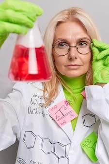 Scheikundige doet wetenschappelijk onderzoek chemische test in laboratorium houdt kolf met rode vloeistof draagt bril witte mantel poseert binnen. biochemie of farmaceutische ontwikkeling