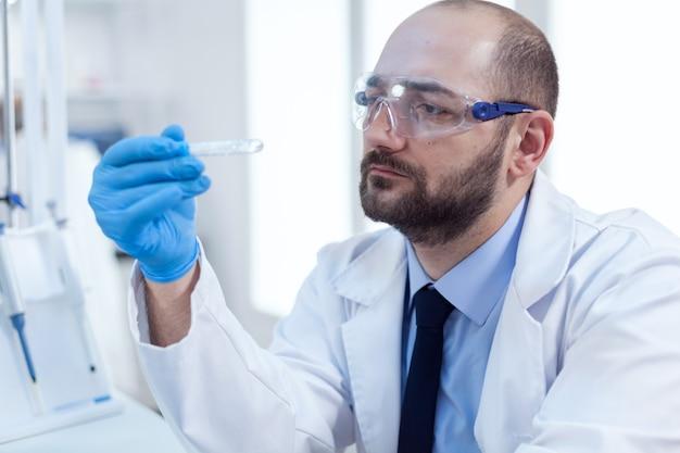Scheikundige wetenschapper houdt reageerbuis van glas in zijn hand voor medicijnexperiment. onderzoeker in biotechnologie steriel laboratorium met analyse in buis met handschoenen en een veiligheidsbril.