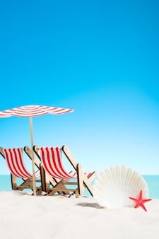 Schelpen en twee ligbedden onder de paraplu op het strand, lucht met kopie ruimte