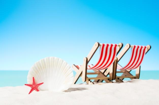 Schelpen en twee ligbedden op het strand
