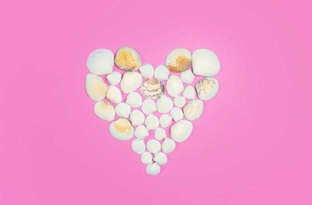 Schelpen op een gekleurde achtergrond. hartvorm gemaakt van zeeschelpen. hoge kwaliteit foto