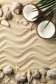 Schelpen, zeesterren, kokos en palmtak op zee zand, ruimte voor tekst