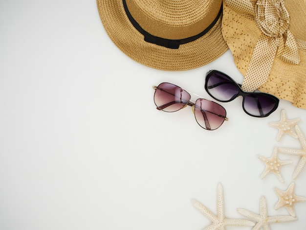 Schelpen, zeesterren, strohoeden, zonnebril op een witte achtergrond