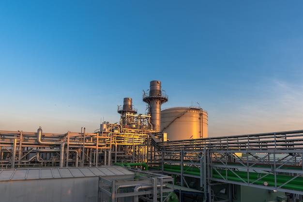 Schemeringfoto van elektrische centrale, aardgas gecombineerde cyclus, gasturbine generator en stapel
