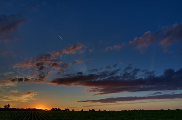 Schemeringhemel met wolken bij dageraad boven een veld met landbouwplantages