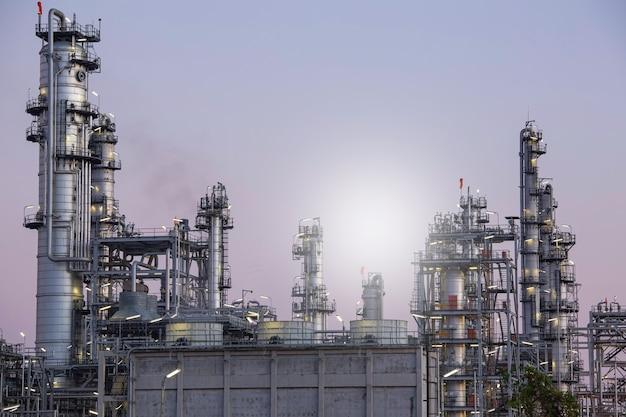 Schemerscène van tankolieraffinaderij en torenkolom van de petrochemie-industrie in het zonlicht van de bouwplaats