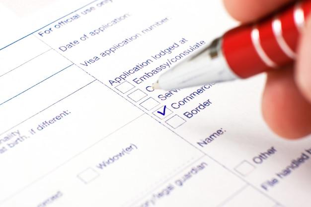 Schengenvisum, vragenlijst. hand met pen die een vragenlijst voltooit.