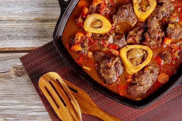 Schenkel van rundvlees gekookt in ijzeren koekenpan met groente. detailopname.