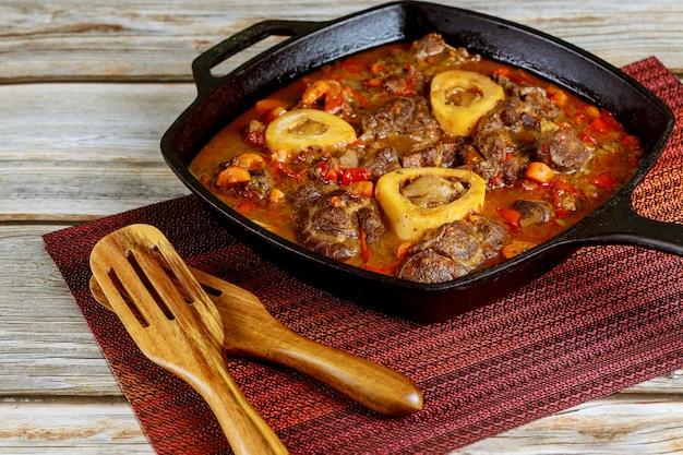 Schenkel van rundvlees gekookt in ijzeren koekenpan met groente.