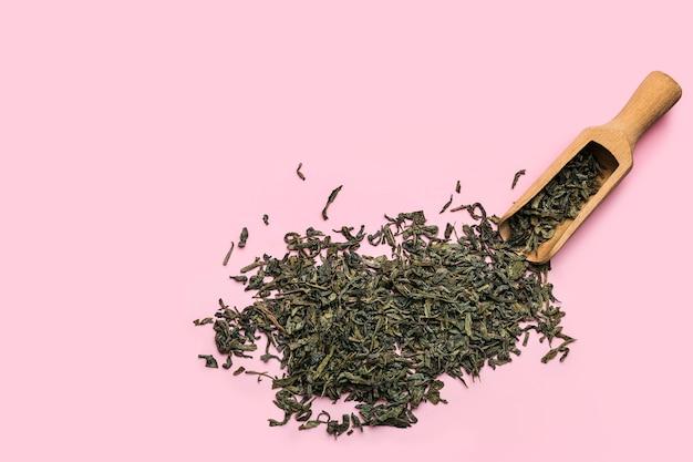 Schep met droge groene thee op gekleurd oppervlak