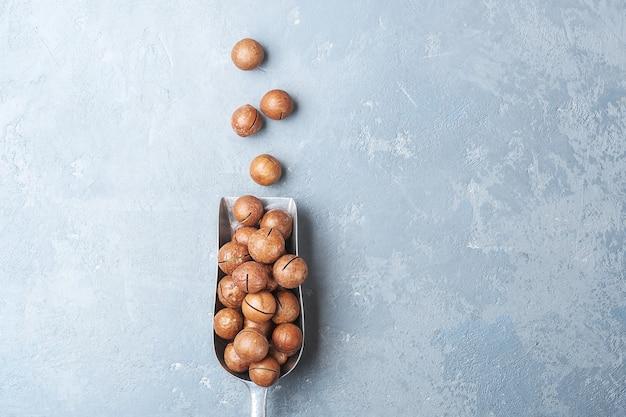 Schep met macadamia-noot op een betonnen tafel