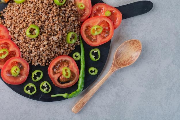 Schep naast een houten plank met boekweit, peper en tomaat op een marmeren ondergrond