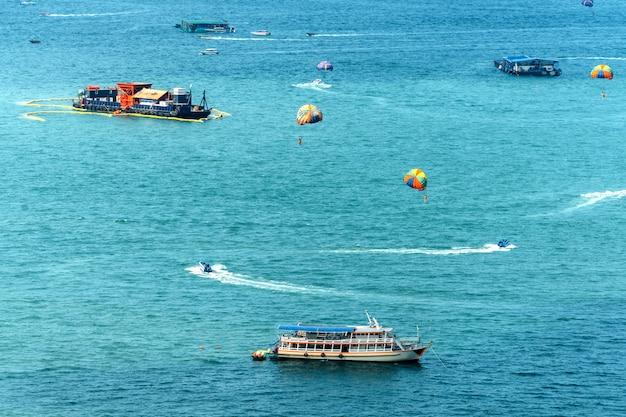 Schepen die over het overzees met toerist drijven die parasailing in pattaya, chonburi, thailand spelen.