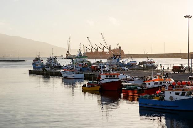 Schepen en boten in zeehaven op zonsondergang.