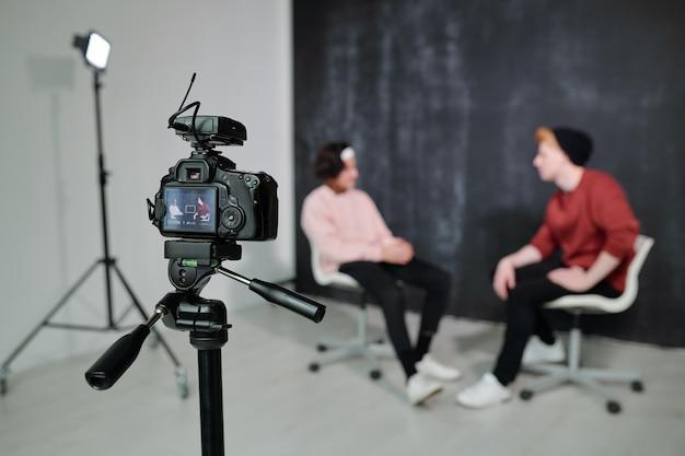 Scherm van digitale videocamera met twee vloggers die op stoelen voor elkaar zitten en in studio praten
