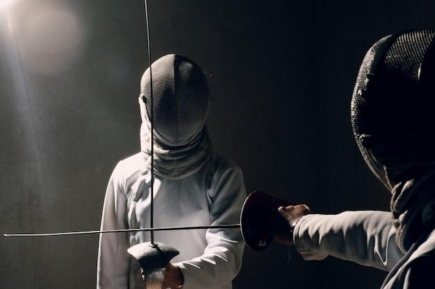 Schermer vrouw met schermend zwaard. schermers duel concept.