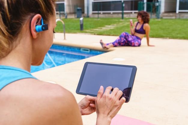 Schermmodel van fitnessvrouw die buiten een online sportles kiest. horizontaal zijaanzicht van een jonge vrouw die verbinding maakt met technologie naar een gymles met vrienden naast een zwembad.