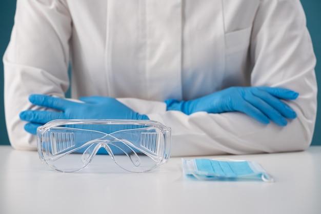 Scherp geschoten op plastic bril en een beschermend masker voor de veiligheid van een paramedicus op het werk met infectieziekten horizontaal met een wazige muur van een verpleegster in een kamerjas