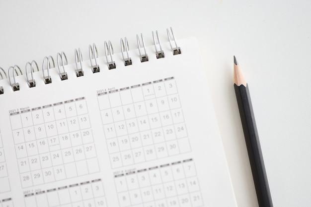 Scherp houten potlood liggend in de buurt van papieren kalender voor close-up