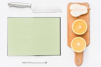 Scherp mes; lege pagina notitieblok; pen; gehalveerde sinaasappelen en peer op witte achtergrond