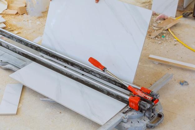 Scherpe arbeider die met vloertegel werken die industrieel materiaal snijden bij het werk van de reparatievernieuwing