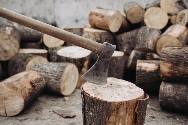 Scherpe bijl die in een stomp tussen gesneden hout wordt geplakt