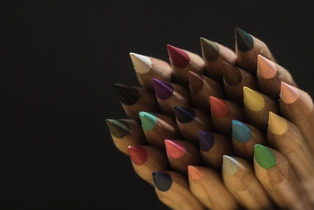 Scherpe kleurpotloden op een zwarte achtergrond. kopie ruimte