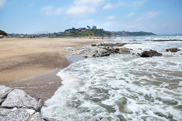Scherpe stenen en oceaanwater op zandig strand van bidart frankrijk