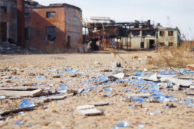 Scherven van glas en leisteen liggen op een betonnen weg verlaten industriële gebouwen.