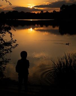 Schets van een jongen bij zonsondergang op het meer