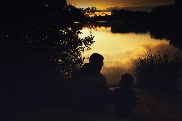 Schets van een jongen met papa bij zonsondergang op het meer