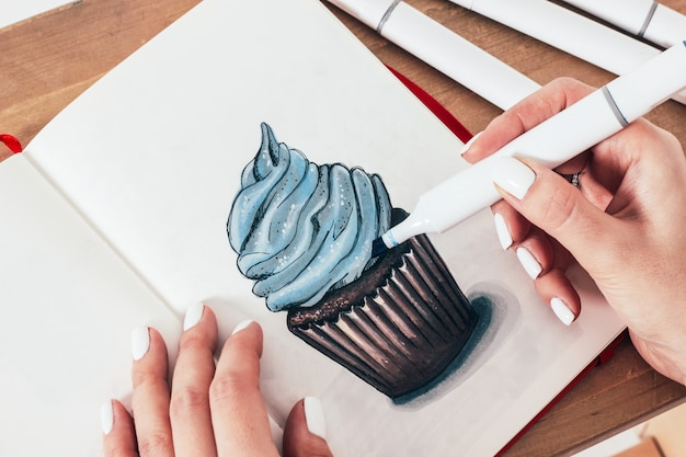 Schetstekening van cupcake door tellers in sketchbook
