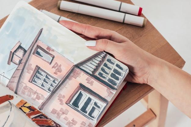 Schetstekening van de oude bouw door tellers in sketchbook met vrouwenhanden