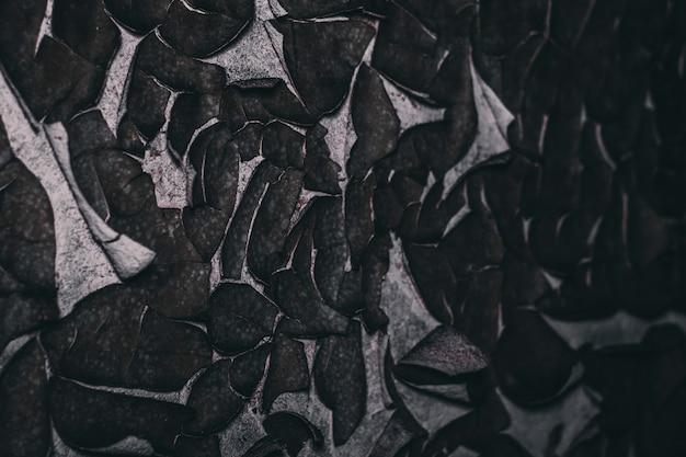 Scheuren en schimmel op de afbladderende stukjes verf vormen een textuur