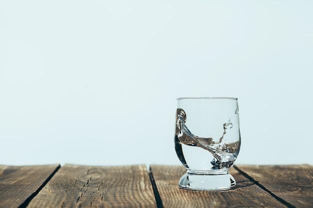 Scheutje water in een glas op hout