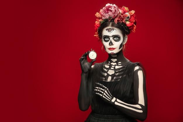 Schiet op. jong meisje zoals santa muerte saint dood of suikerschedel met lichte make-up. portret geïsoleerd op rode studio achtergrond met copyspace. het vieren van halloween of dag van de doden. verkoop