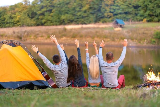 Schiet van achteren. een groep gelukkige vrienden die aan de rivier kamperen, dansen, handen omhoog houden en genieten van het uitzicht. vakantie leuk