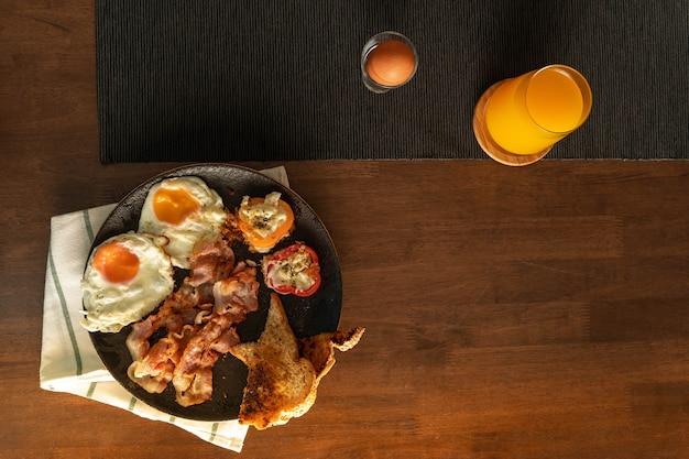 Schiet vanuit een bovenaanzicht, ontbijt, eenvoudig recept, gebakken eieren, spek, gegrilde paprika en brood