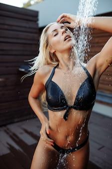 Schieten in de aquazone met vallende waterdruppels. een meisje met blond haar in een zwart zwempak onder een koude douche in een recreatiecomplex. zomer vakantie reclame concept bij het zwembad, waterpark.