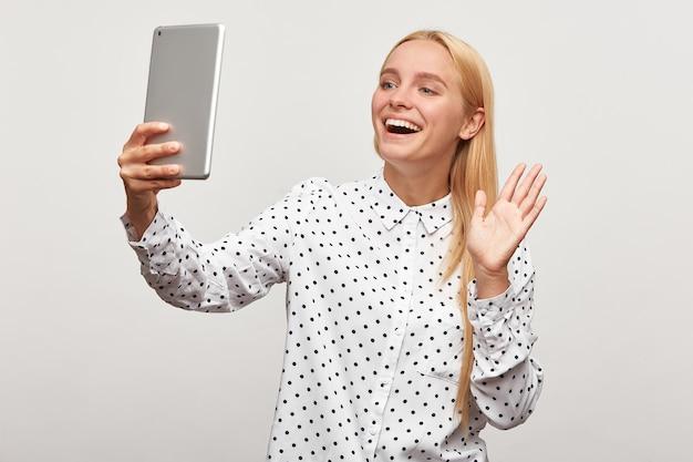 Schieten van een blonde jonge vrouw met tablet in de hand, een videogesprek voeren of video opnemen